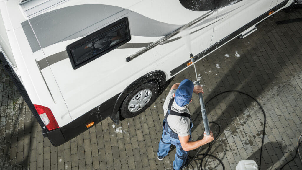 A man uses a pressure washer which is a great and useful RV cleaning product to clean the outside of his RV.