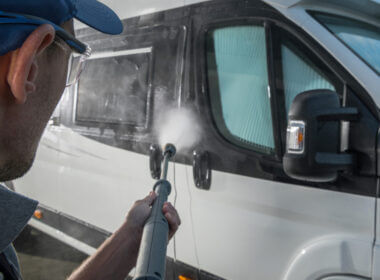 A man hoses down an RV and uses some of the best RV cleaning products to keep his RV in tip top shape.