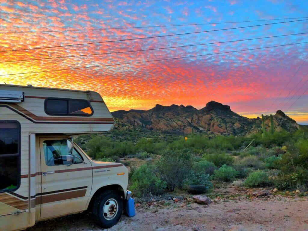 RV parked in Quartzite Arizona with the mountains in the background and a sunset
