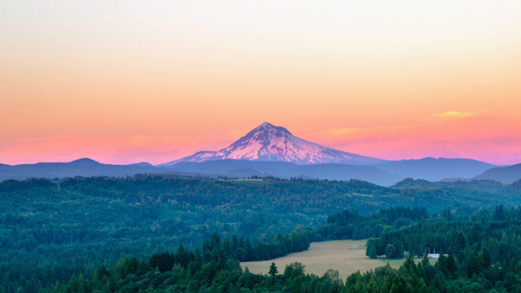 Mt Hood in Oregon glows in the sunset colors with the Columbia River and forest land below.