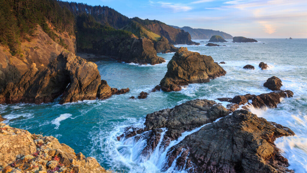 The Oregon Coast rumbles with beautiful waves crashing against the rocky cliffs and trees down to the coast line.