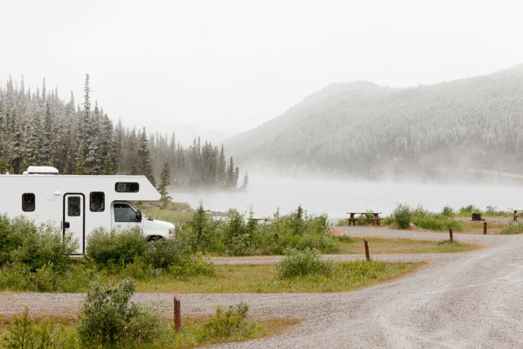 Camper parked beside a lake on a rainy and misty day during dangerous flood warnings.