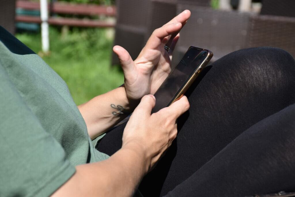 A woman on her phone in a campground trying to use bluetooth to connect to her power watchdog 30amp.