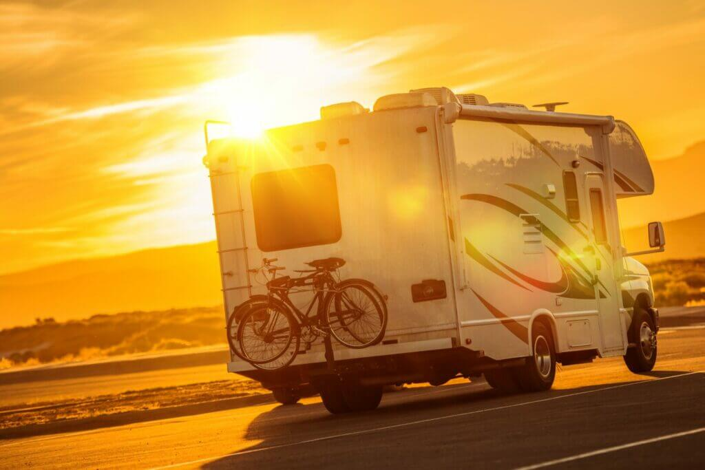 A couple in retirement driving an RV down the interstate into the sunset.