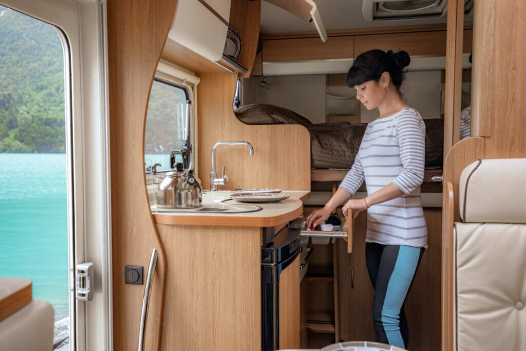 A woman cleaning her kitchen in an RV parked beside the lake.