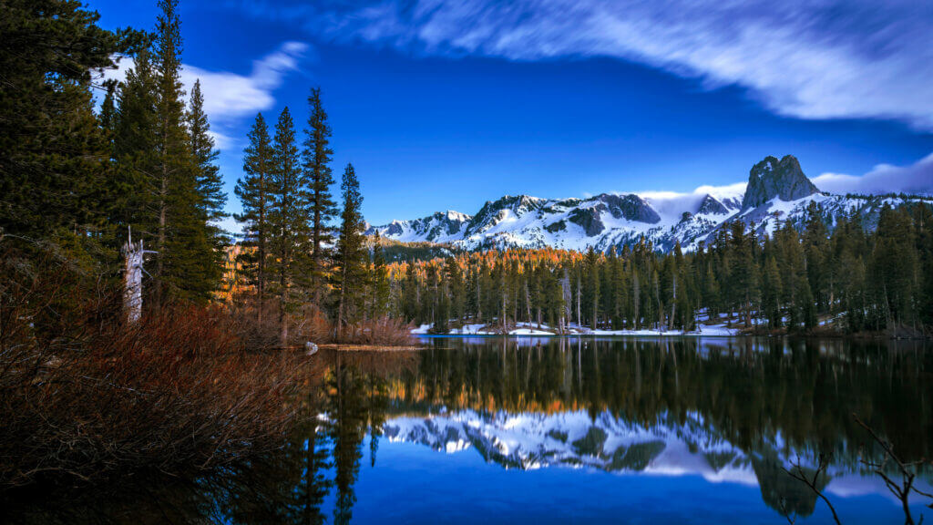Mammoth Lake glows blue as the sun sets over the mountains and trees around.