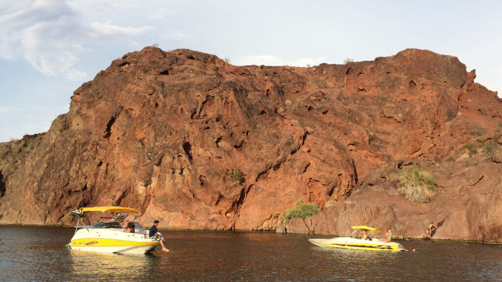 Two boaters sit on the surface of Lake Havasu with desert rocks in the background.