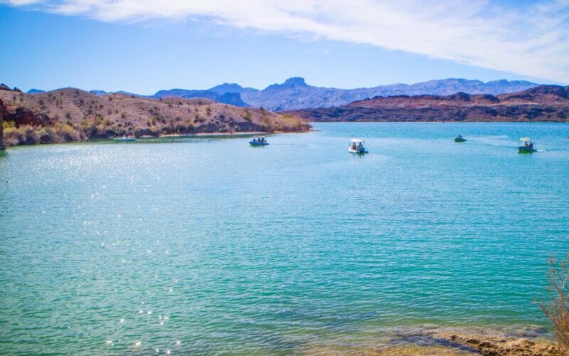 Boats sit on top of Lake Havasu and the bright blue green waters with desert mountains around.