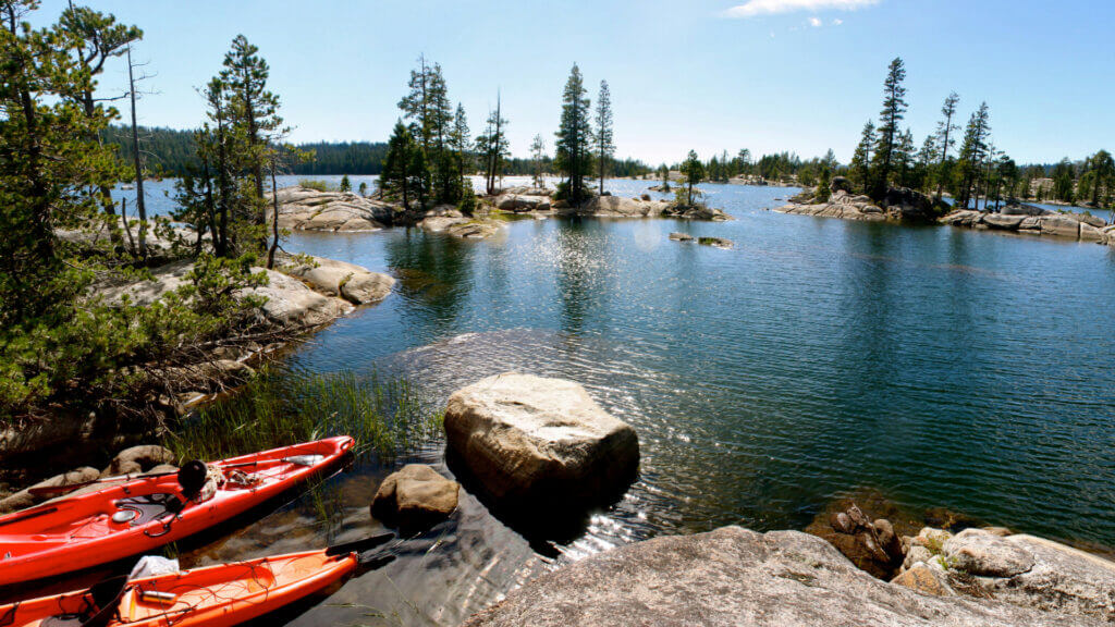 Two kayaks sit on the shoreline ready to go into the Utica Reservoir with rocky islands and trees throughout.
