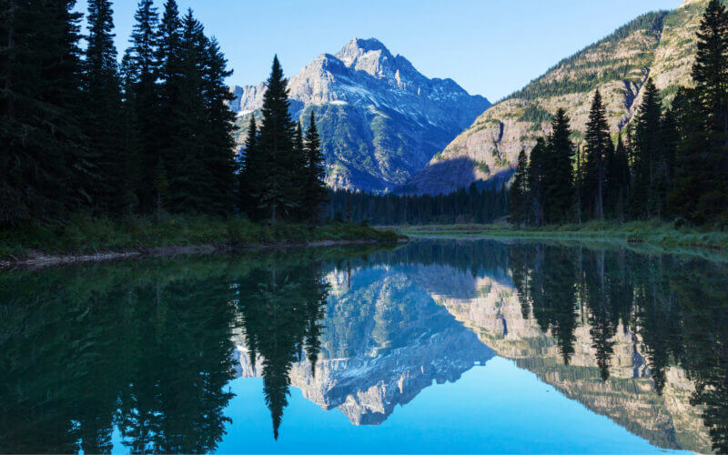 A mountain reflects on the surface of a lake in Montana.