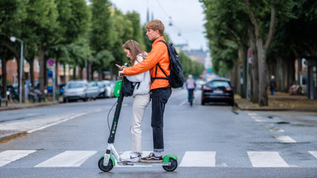 A couple navigate the city together on a Lime scooter.