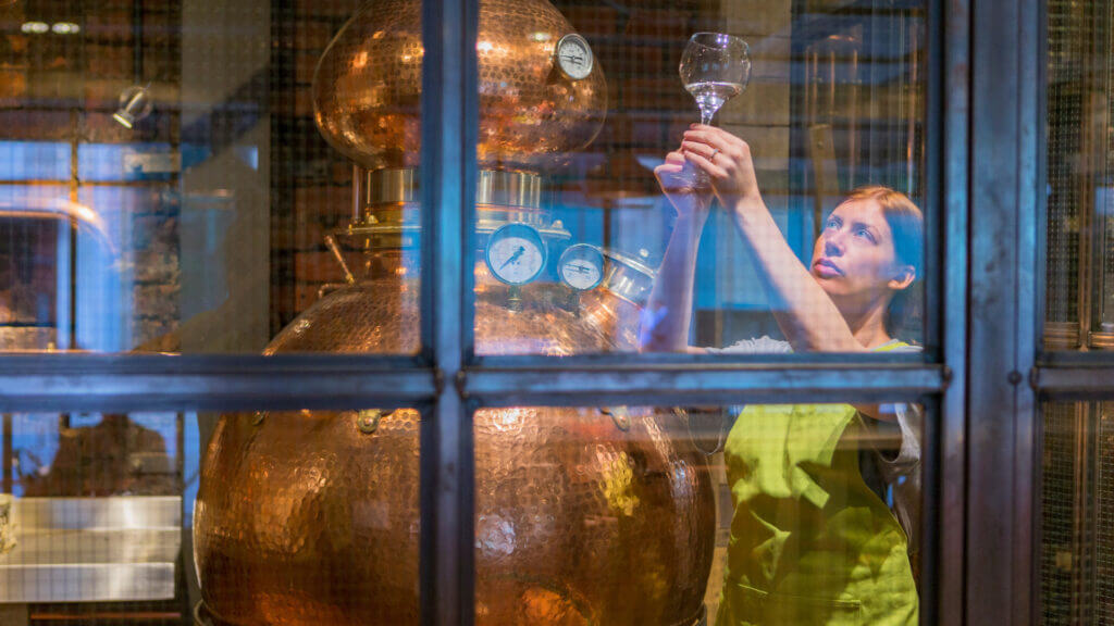 A woman checks the alcohol quality in a distillery.