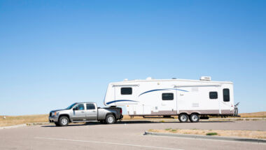 A dually truck tows a large fifth wheel trailer across a parking lot in the desert.