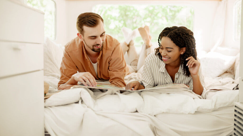 A man and woman smile and look at a map while laying on their RV bed with luxurious RV sheets.