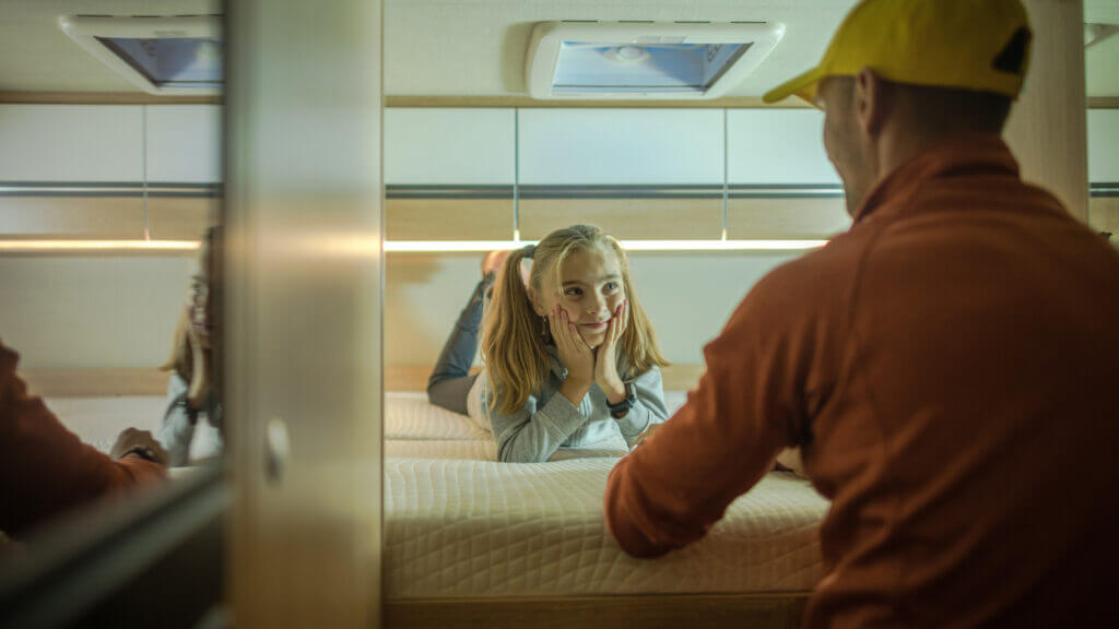A girl lays on an RV bed and looks at her dad. What RV sheets are best for their mattress?