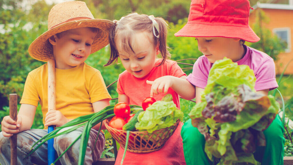 While in Des Moines, you must visit the Living History Farms to learn all about farming and trades. Three kids enjoy farm vegetables they picked.