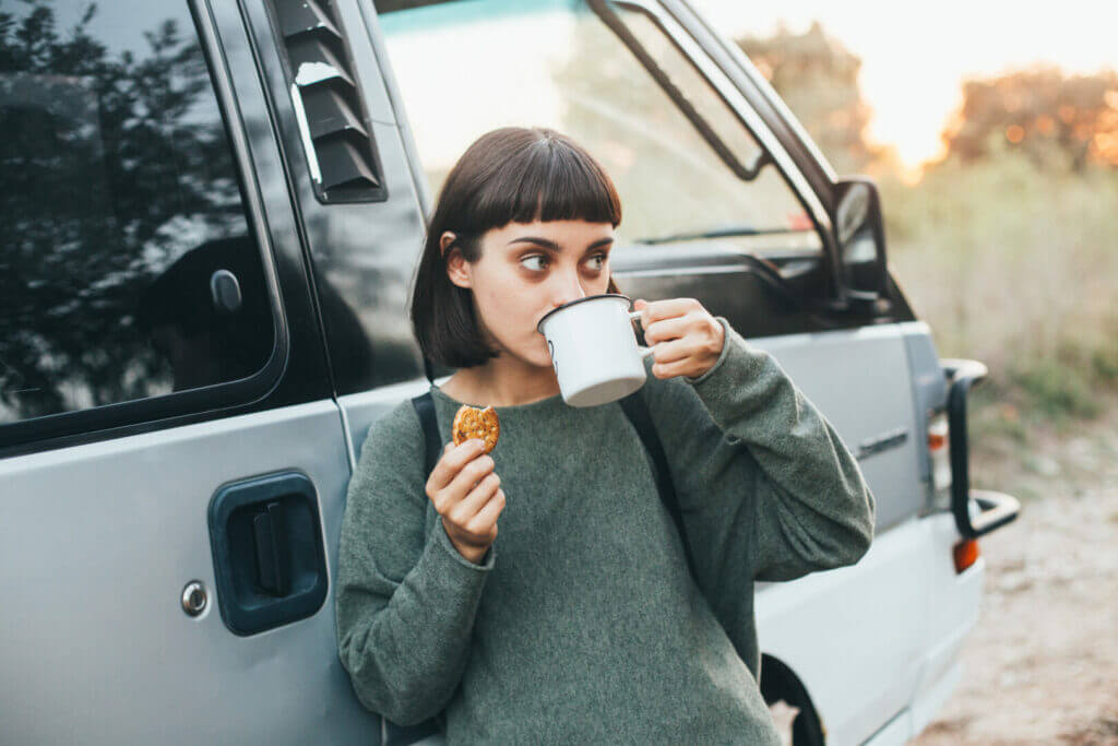 A woman enjoying breakfast and coffee outdoors.