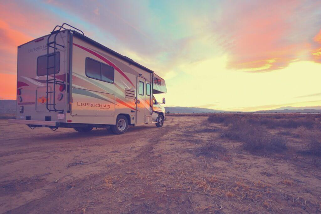 An RV driving into the sunset on its way to Arco, Idaho.