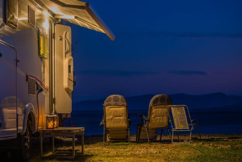 An RV parked beside a lake at with the lights on.