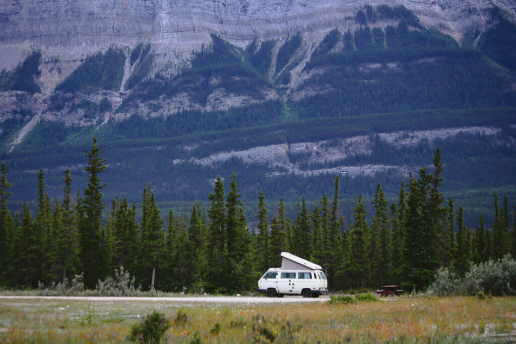 A pop-up camper driving down the highway beside a forest.
