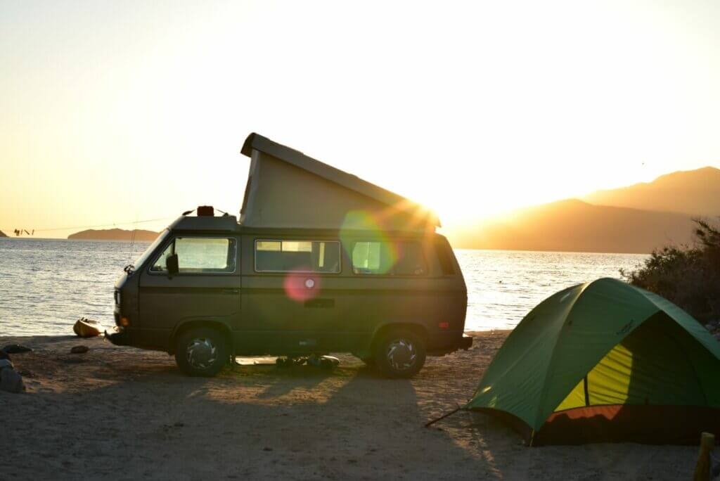Pop-up camper camping beside a lake with a tent.