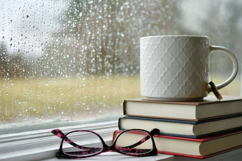A coffee mug on a pile of books with a wet window in the background