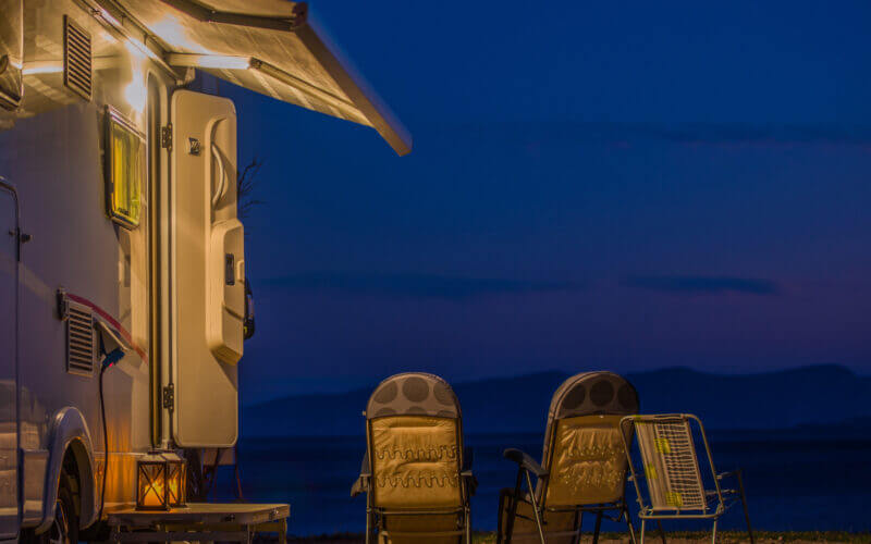 A dark blue night is lit up outside of an RV by the awning lights.