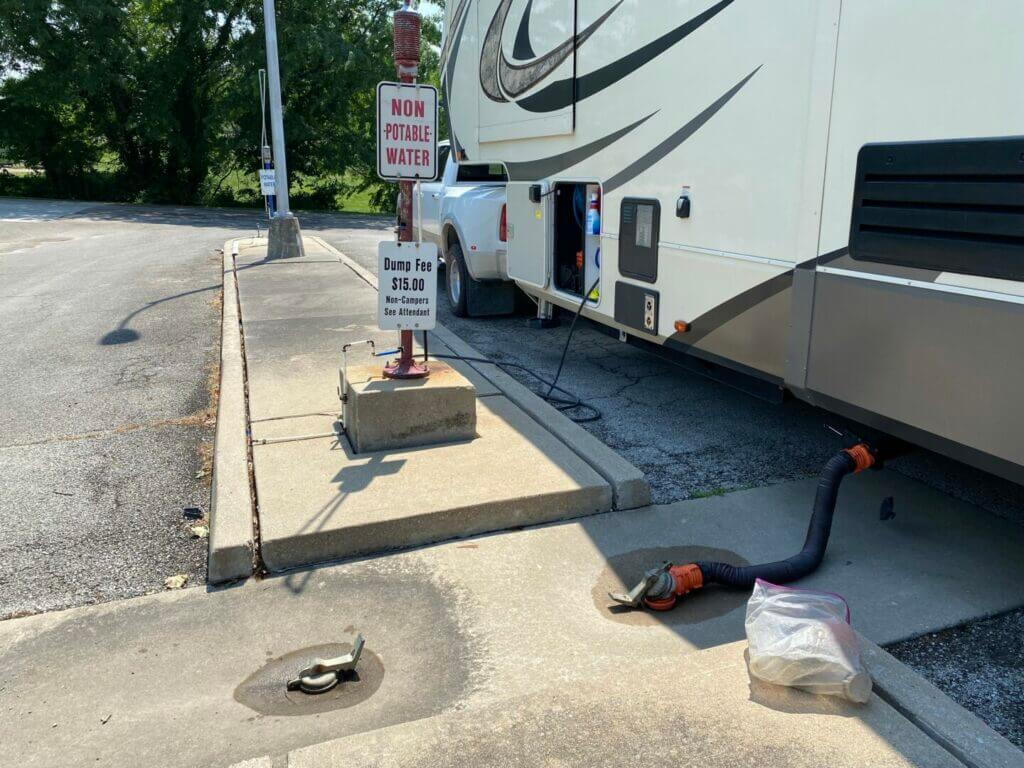 An RV parked at a dump station using the best RV sewer hose to dump its tanks