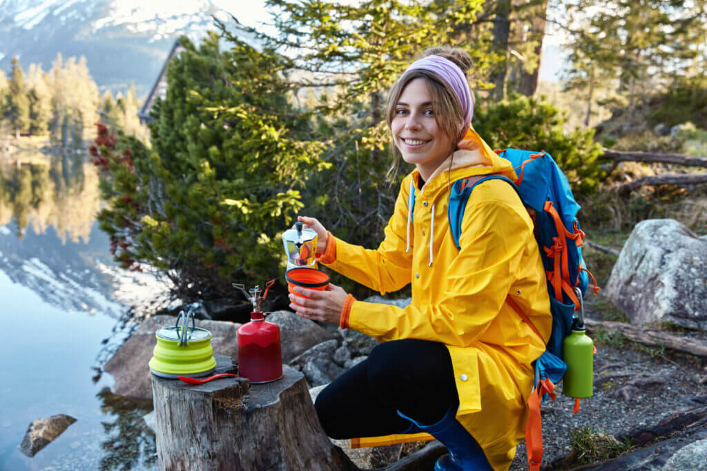 Woman enjoying coffee at her campsite in the forest.