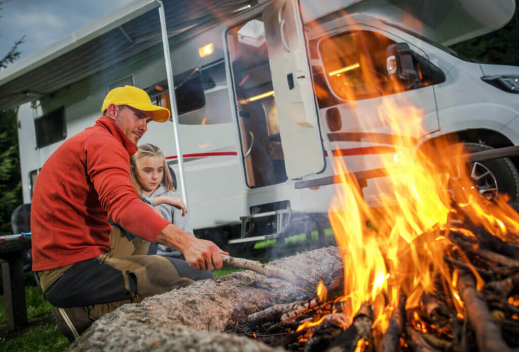 Family tending to fire while camping.