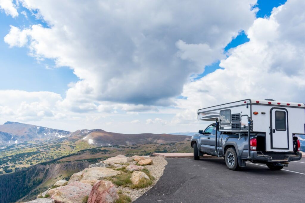 Truck camper parked at a view point overlooking mountains.