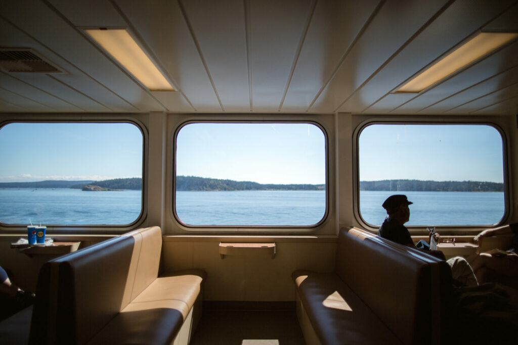 inside of a ferry on the water with mountains outside the window