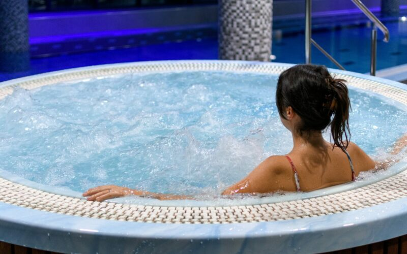 A woman relaxes in a blue hot tub all to herself.