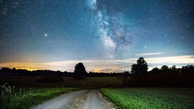 A dirt road leads into a dark starry night.