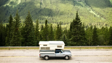 A truck camper cruised along a highway next to green mountain forests.