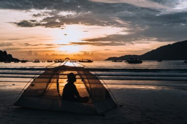 A woman sits in a tent on a beach at sunrise.