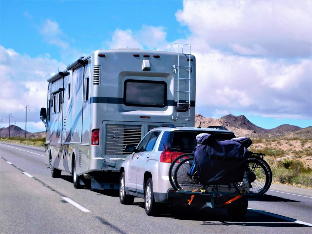 Motorhome with a car driving to its next destination.