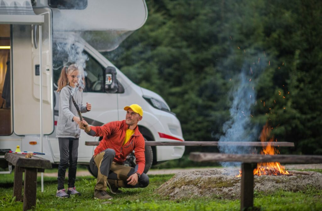 Father and daughter tending to fire at campground.