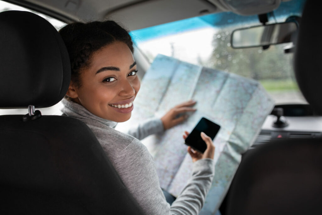 Woman using a map and her phone to find the best route to drive.