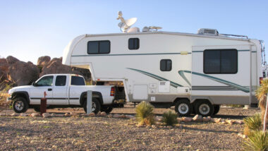 A truck has a fifth wheel towed behind it and is ready to camp!