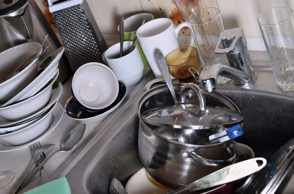 A huge pile of unwashed dishes in the kitchen sink and on the countertop. Small spaces get dirtier faster when you consider selling your house to live in an RV
