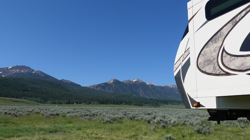 The front of a fifth wheel with mountains and blue skies in the background