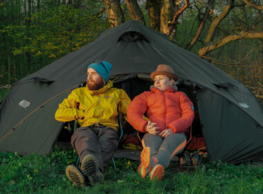 outdoors couple (man and woman) sitting in front of a tent on camping chairs.