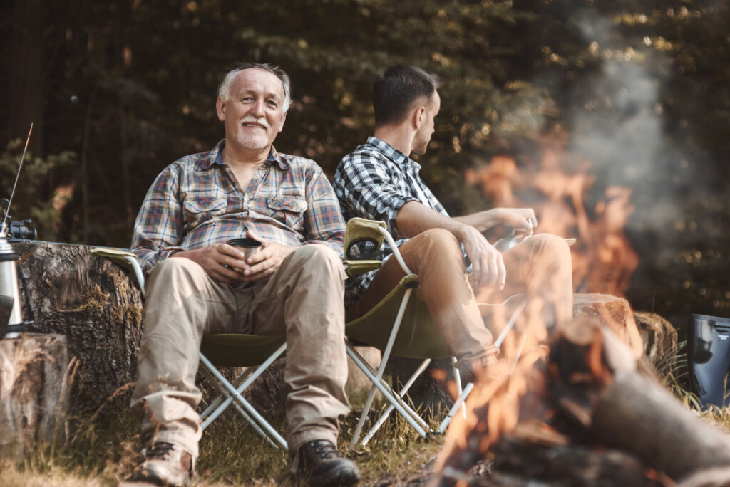 Father and son using their heated camping chairs on vacation.