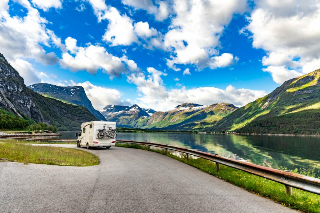 RV driving down the highway beside a lake.