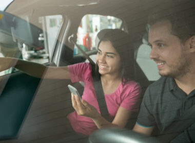 A man and woman are looking their phone gps app.