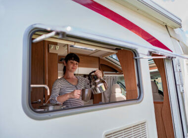 A woman cooking a meal inside of her RV.