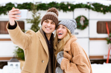 A couple taking a photo in the snow enjoying their new RV cell phone booster.