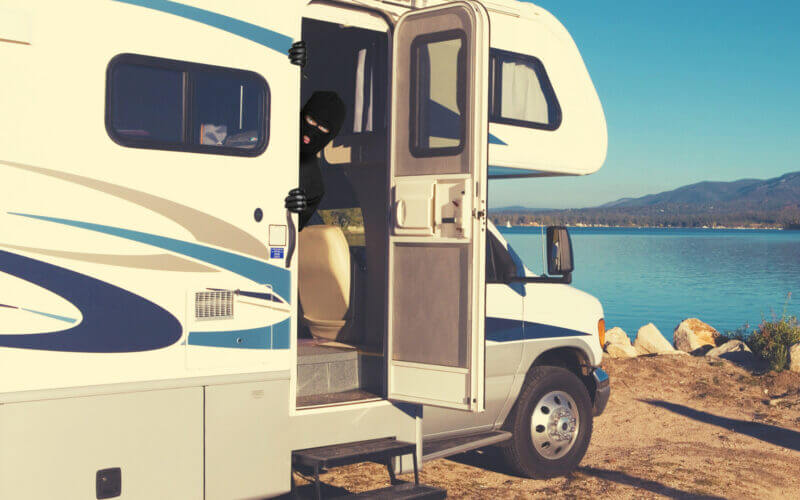 An RV is parked along water and a thief is poking his head out of the open door.