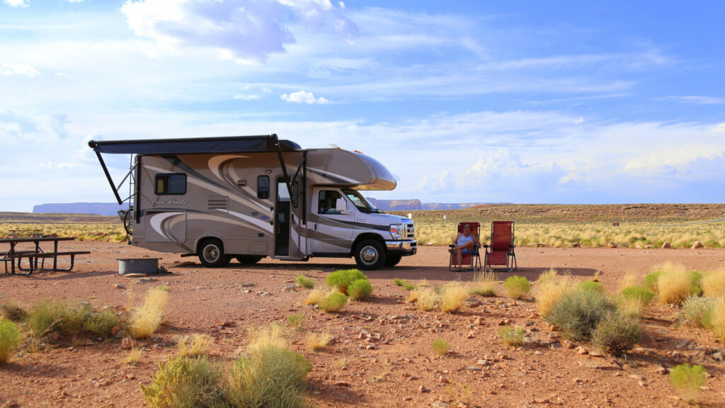 A lady sits on a lawn chair outside of here RV that is dry camping in the desert.